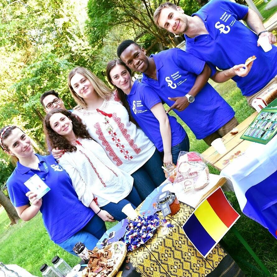 Young people standing close to a table with romanian flag and food